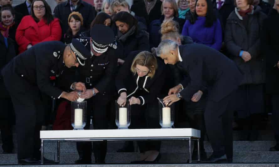 Mayor Sadiq Khan, right, with the home secretary, Amber Rudd, lights a candle in Trafalgar Square, Thursday.