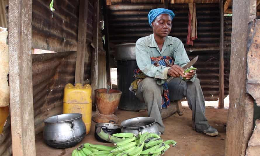 A woman in Ghana cutting bananas. Preparing food is often done by the women of a family.