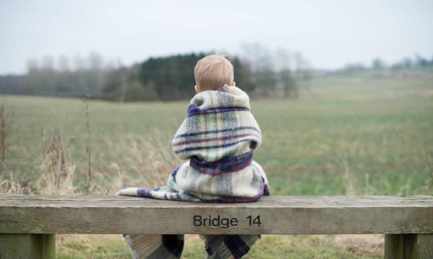 Rear view of a boy sitting on bench, wrapped in warm blanket.
