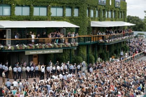 Roger Federer shows the trophy to the huge crowd at the front of the clubhouse