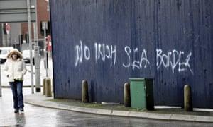 Aa woman walks past past graffiti with the words 'No Irish Sea Border' in Belfast city centre in February.