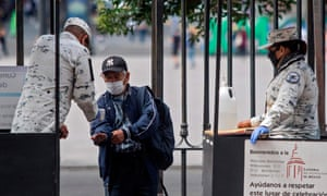 A member of National Guard wearing a face mask offers alcohol gel to a man as he enters to attend the first mass in the Metropolitan Cathedral following the resumption of activities, after measures and restrictions to fight the spread of coronavirus were eased in Mexico City.