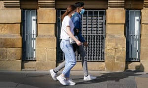A couple wearing face masks walk through the centre of Newcastle.