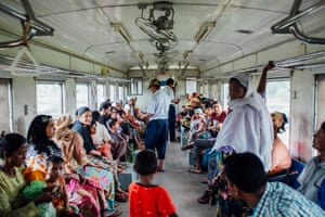 Train conductors check and sell train tickets in the Rohingya compartment of the train