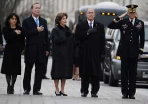 Former president George W Bush, the deceased president's son, with his wife Laura, brother Neil Bush and his wife Maria, stand as the flag-draped casket of George HW Bush is carried from the US Capitol.