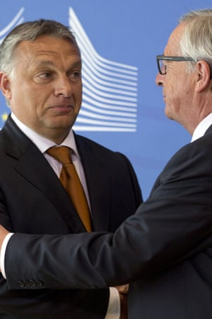 European Commission President Jean-Claude Juncker, right, shakes hands with Hungarian Prime Minister Viktor Orban.