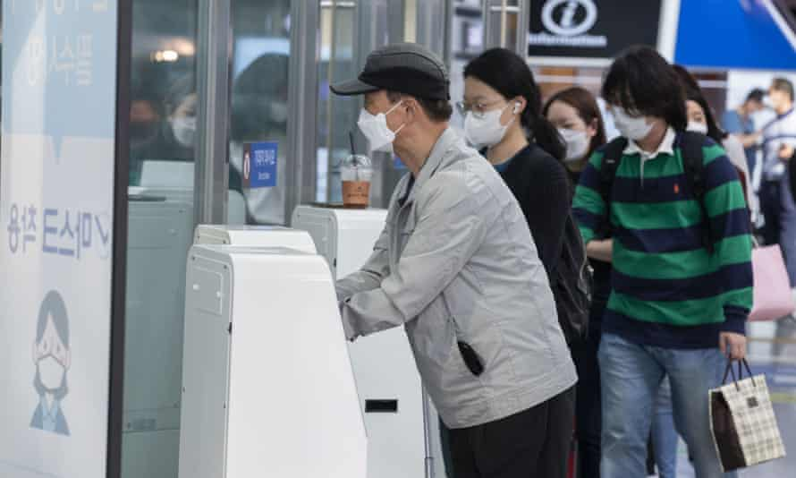 People wearing face masks sanitise their hands at Seoul Station in Seoul, South Korea.