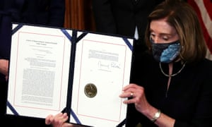 House speaker Nancy Pelosi shows the article of impeachment against Donald Trump after signing it in an engrossment ceremony at the Capitol.