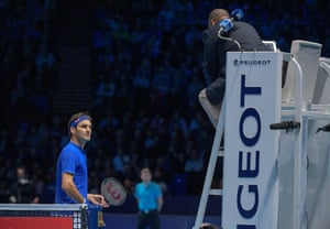 Roger Federer talks with the umpire after Alexander Zverev stopped playing when a ballboy dropped a ball.
