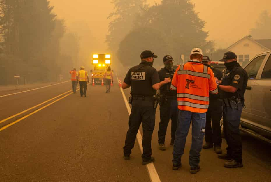 Oregon state police and an Oregon Department of Transportation official confer at a roadblock at the McKenzie Fire District Station in Leaburg, Oregon, on 8 September.