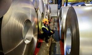 A worker inspecting rolls of steel.