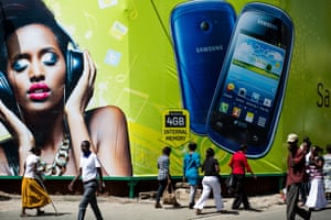 Pedestrians pass beneath a giant mobile phone advertisement in Nairobi, Kenya