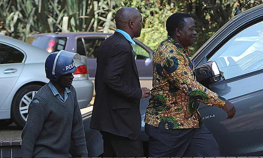 Zimbabwe war veterans' association secretary general Victor Matemadanda is escorted by police to a court hearing.