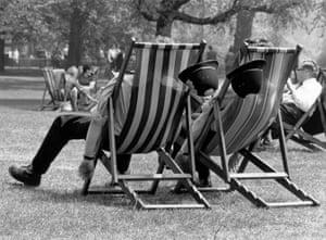 Two London policemen take a break from patrolling in a park