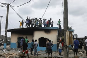 People stand on the roof of a police station set on fire by protesters during a demonstration against the decision of Ivory Coast President Alassane Ouattara to run for a third term in the next presidential election, in Bonoua, Ivory Coast, on 14 August.