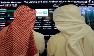 Investors monitor the Saudi stock exchange during Saudi Aramco's IPO on the Riyadh stock market, in December.