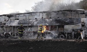 Firefighters work on a burned bus on the highway between Guadalajara and Leon as violence raged across Jalisco state.