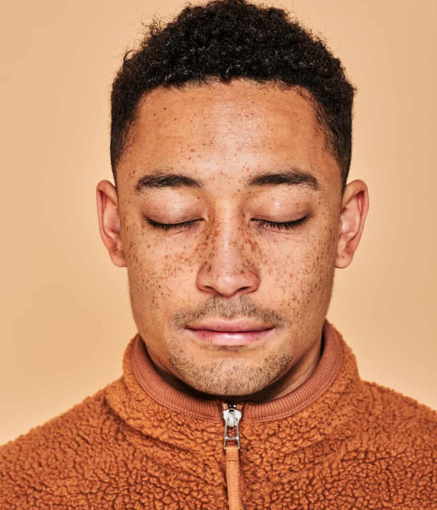 Loyle Carner in an orange fleece top, zipped up, and with his eyes closed.