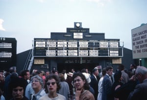 Spectators pass the Order of Play boards in 1963