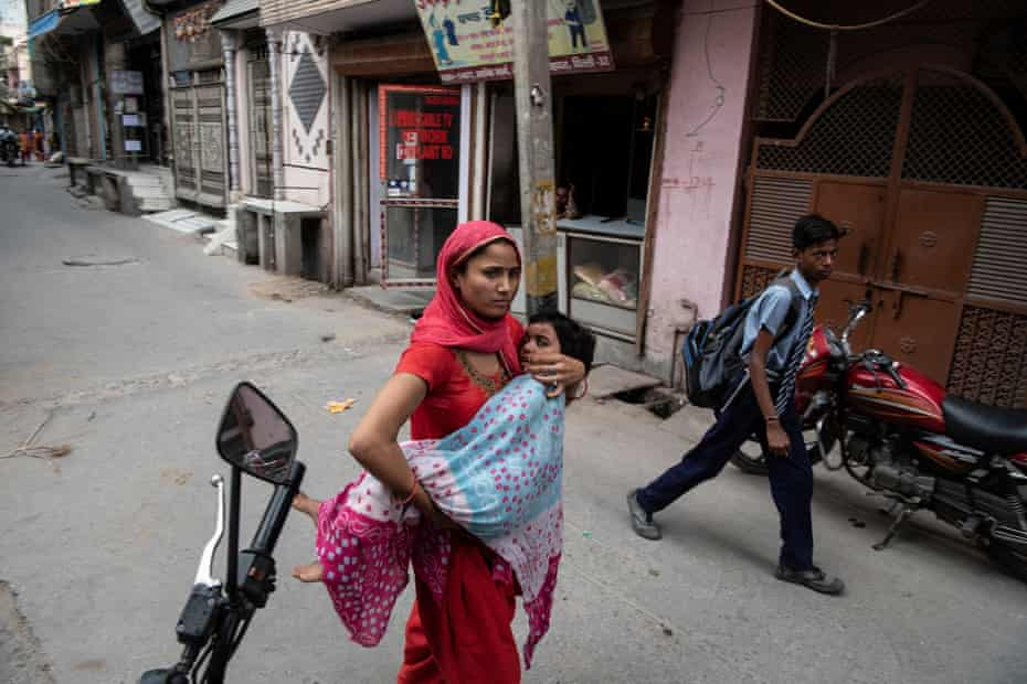 A woman carries a child to Sagar clinic.