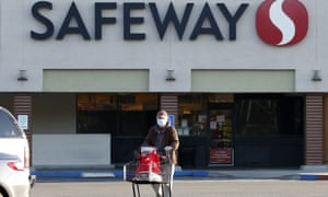 Wearing a mask for protection against the coronavirus, Henry Powell heads to his car after shopping at a Safeway store in Sacramento
