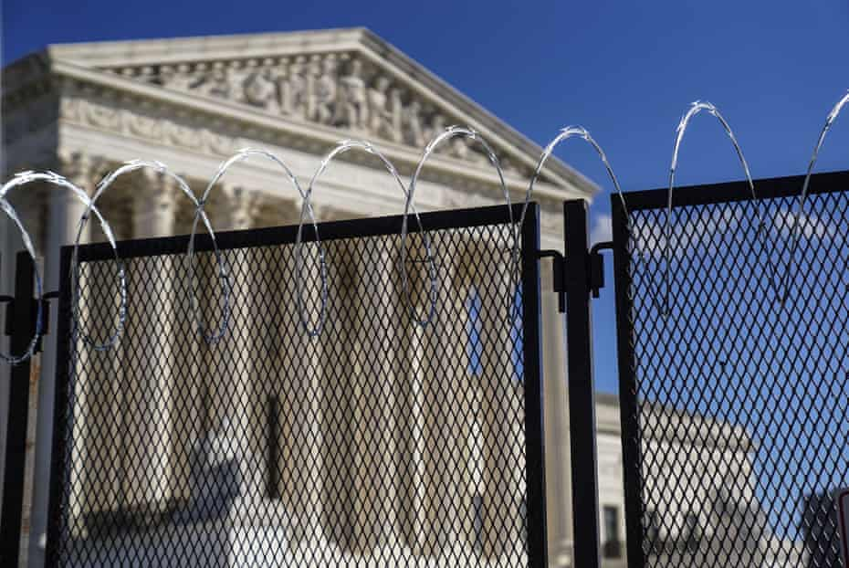 The supreme court building in Washington DC is surrounded by fences and barbed wire.