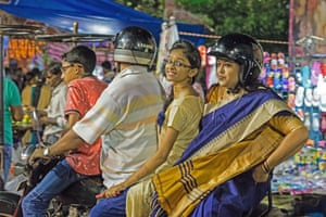 A colourful market scene in Kolkata, India and on a motorbike sit four people. At the back are two women who are looking at the camera: one smiles, the other (wearing a helmet) looks off into the distance.