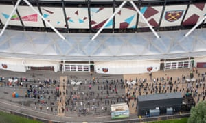 People queue outside an NHS Vaccination Clinic at West Ham's London Stadium in Stratford, east London.