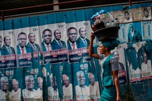 A woman with a large plastic bucket filled with drinks and food passes by a wall covered with posters of presidential candidate Atiku Abubakar of the People's Democratic Party, the official opposition party, in Lagos. Nigerians took part in national elections on 16 February when current president Muhammadu Buhari sought re-election for the ruling party, All Progressives Congress.