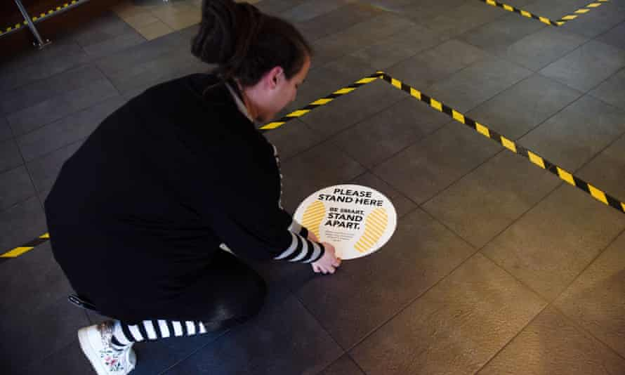 A New Zealand museum worker removes social distancing markers as coronavirus regulations are lifted in the country.