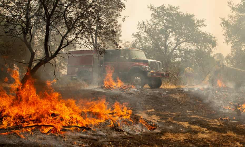 Firefighters douse a hotspot near various homes as the Carr fire continues to burn near Redding, California, over the weekend.