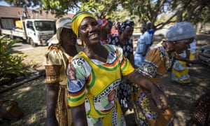 A woman wearing a dress bearing the face of Robert Mugabe joins with others to sing political songs in his home village of Kutama