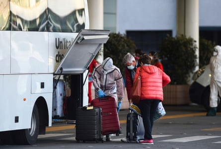 A man in a hazmat suit helps two passengers load their bags onto a bus