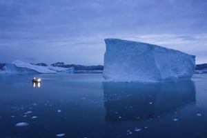 A boat navigates icebergs at night in eastern Greenland