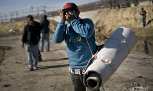 A migrant carrying a roll of carpet wipes his face after US border agents fired tear gas at a group who had pushed past Mexican police at the Chaparral border crossing.
