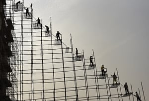 Greater Noida, India Labourers stand on scaffolding to move steel rods from the ground to the top of a planned hospital building. Building work in the region has resumed after authorities lifted a ban on construction imposed to combat air pollution.