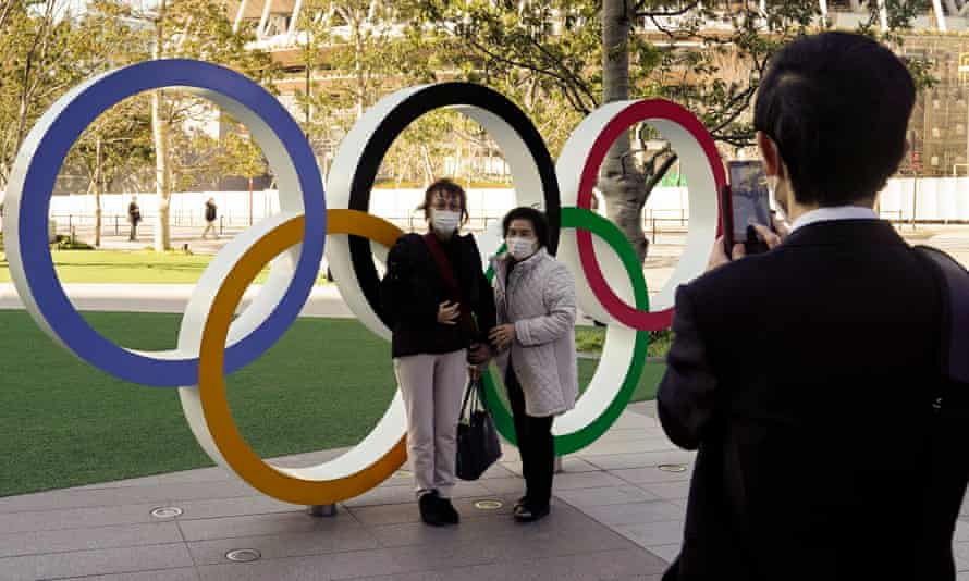Visitors wearing face masks take a photo at the Olympic Rings monument in front of the Japan Olympic Committee headquarters in Tokyo