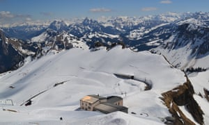 A view of the Alps from Rochers de Naye with the cafe and looping rail track in the foreground.