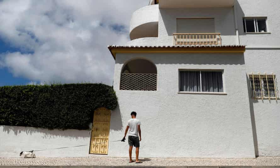 A man walks with his dog below the apartment where three-year-old Madeleine McCann disappeared in 2007, in Praia da Luz, Portugal.