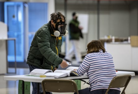 Robert Forrestal, left, wears a full face chemical shield to protect against the spread of coronavirus, as he votes at the Janesville Mall in Janesville, Wisconsin.