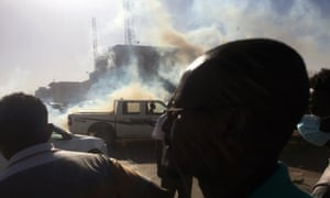 A pick-up truck drives past tear gas fired to disperse demonstrators during a protest demanding president Omar Al-Bashir in Khartoum.
