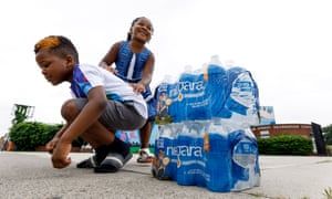 Children play next to packages of bottled water at a city-run water distribution site in Newark, New Jersey, on 16 August.