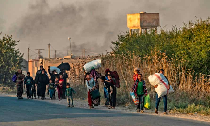 Civilians flee with their belongings amid Turkish bombardment of Ras al-Ayn.