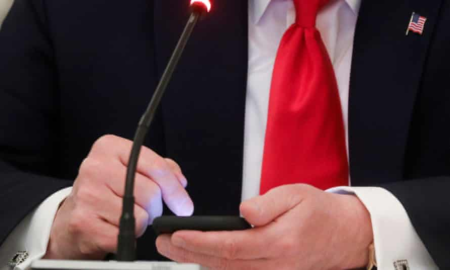 Donald Trump taps the screen on a mobile phone on 18 June at the approximate time a tweet was released from his Twitter account.