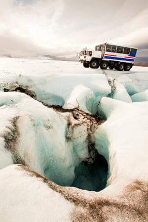 A 20 tonne ice explorer truck next to a Moulin, or sink hole for meltwater