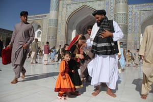 Afghans leave after offering Eid al-Adha prayers at a mosque in Herat, Afghanistan