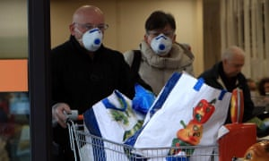 People wearing protective face masks shop at a supermarket in Casalpusterlengo, one the northern Italian towns placed under lockdown due to the new coronavirus outbreak.