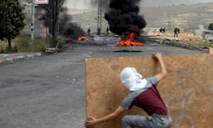 Palestinian demonstrator takes cover during a protest near Ramallah, in the occupied West Bank