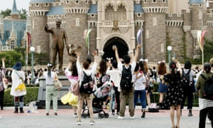 Visitors wave to Disney characters performing at Tokyo Disneyland in Urayasu, near Tokyo, Wednesday, 1 July 2020.
