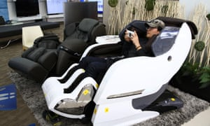 A customer tries out a massage chair. One Japanese man fell asleep in a chair and was reportedly locked in a store at night.